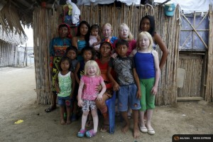 "Four albino sisters, from L-R, Iveily, Donilcia, Jade and Yaisseth Morales, who are part of the albino or ""Children of the Moon"" group in the Guna Yala indigenous community, pose for a photograph with their mother, brothers and sisters outside their house on Ustupu Island in the Guna Yala region, Panama April 24, 2015. REUTERS/Carlos Jasso"