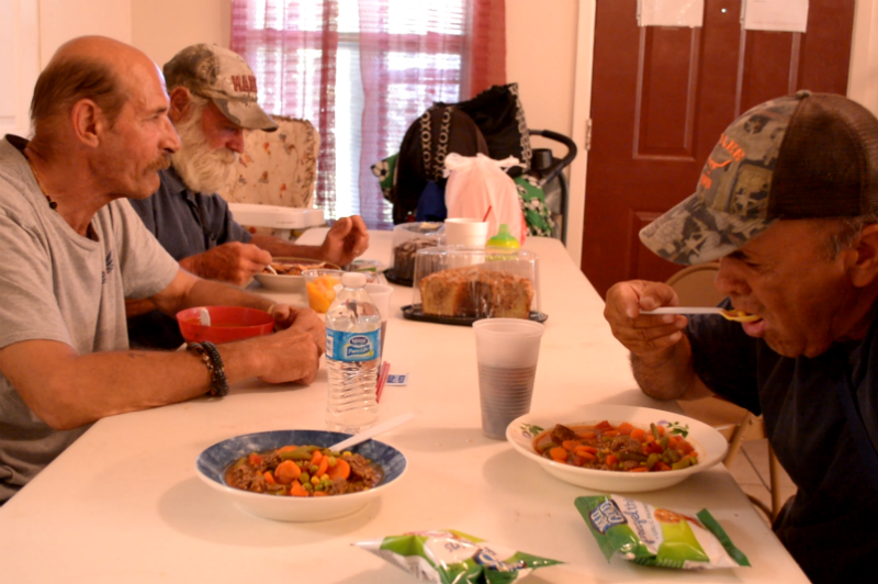 Three men share a hot meal together Monday at San Marcos' Southside Community Shelter. The shelter serves a hot dinner every day. Photo by Jesse Louden/VoiceBox Media