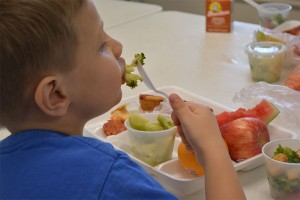 Dreyden Crawford, 6, enjoys a nutritious meal at PODER Learning Center on Thursday, June 25. Photo by Jesse Louden/VoiceBox Media