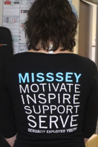 Mentorship and Training Coordinator Liz Longfellow at MISSSEY displaying the organization's staff shirts.