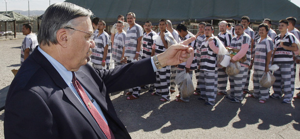 FILE - In this Feb. 4, 2009 file photo, Maricopa County Sheriff Joe Arpaio, left, orders approximately 200 convicted illegal immigrants handcuffed together and moved into a separate area of Tent City, for incarceration until their sentences are served and they are deported to their home countries, in Phoenix.  The Homeland Security Department says it will use 50 immigration agents to screen jail inmates in Arizona's Maricopa County after it revoked Arpaio's authority to use its systems. Homeland Security Secretary Janet Napolitano revoked that authority on Dec. 15 after a Justice Department investigation concluded that Arpaio's office engaged in a pattern and practice of civil rights and constitutional violations and discriminated against Latino inmates in its jails.   (AP Photo/Ross D. Franklin, File)