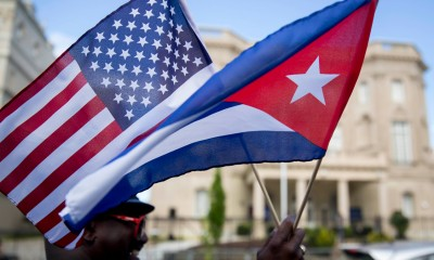 Eduardo Clark holds American and Cuban flags across the street from the Cuban embassy in Washington, D.C., U.S., on Monday, July 20, 2015. A diplomatic freeze that stretched five decades, outlasting the Cold War and nine U.S. presidencies, formally ends Monday when Cuba and the U.S. reopen embassies. Cuban Foreign Minister Bruno Rodriguez will attend a flag-raising ceremony at the Cuban chancery in Washington before meeting Secretary of State John Kerry, who will travel to Havana at a later date. Photographer: Andrew Harrer/Bloomberg via Getty Images