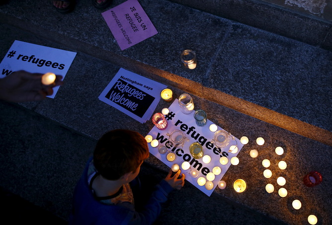 A boy lights a candle during a vigil for refugees in Nottingham, Britain, September 7, 2015.  British Prime Minister David Cameron pledged on Monday to take in up to 20,000 refugees from camps in Syria over the next five years, responding to public pressure to help.  REUTERS/Darren Staples - RTX1RJN7