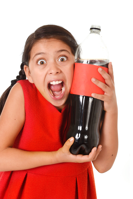 happy female child holding big cola soda bottle against her face in crazy and over excited expression isolated on white background in sugar drink abuse and addiction and sweet nutrition excess
