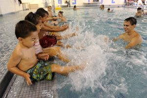 Devon North, a swimming instructor at the Southwest YMCA in Kenyon Boulevard in Denver, teaches a group of children how to use your arms to swim. A report from USA Swimming shows that 60% of Hispanic children can not swim with ease. A study commissioned in 2010 by the U.S Swimming Team and conducted by the University of Memphis looked at the differences between different minorities as it relates to swimming. Several large cities including Denver participated in the study that found that 58 percent of Hispanics have very low or no swimming ability.  These large percentages are in part related to parental fear of water, passed down through the generations and cost prohibited issues. Many of the YMCA's in Denver have tried to combat this issue by offering scholarships to nearly 50 percent of their students. Manuel Martinez/Viva Colorado  North Devon, un profesor de natacion en la YMCA del Suroeste en Kenyon Boulevard, en Denver, ensena a un grupo de ninos a usar sus brazos para nadar. Un informe de EE.UU. Natación muestra que el 60% de los niños hispanos no se puede nadar con facilidad. Un estudio encargado en 2010 por el Equipo de Natación de EE.UU. y realizado por la Universidad de Memphis observaron las diferencias entre las distintas minorías en lo que respecta a la natacion. Varias de las grandes ciudades como Denver participaron en el estudio que encontro que el 58 por ciento de los hispanos tienen la habilidad de nadar muy bajo o nulo. Estos altos porcentajes son, en parte relacionados con el miedo de los padres de agua, pasa de generación en generacion y el costo temas prohibidos. Muchos de los YMCA en Denver han tratado de combatir este problema ofreciendo becas a casi el 50 por ciento de sus estudiantes.