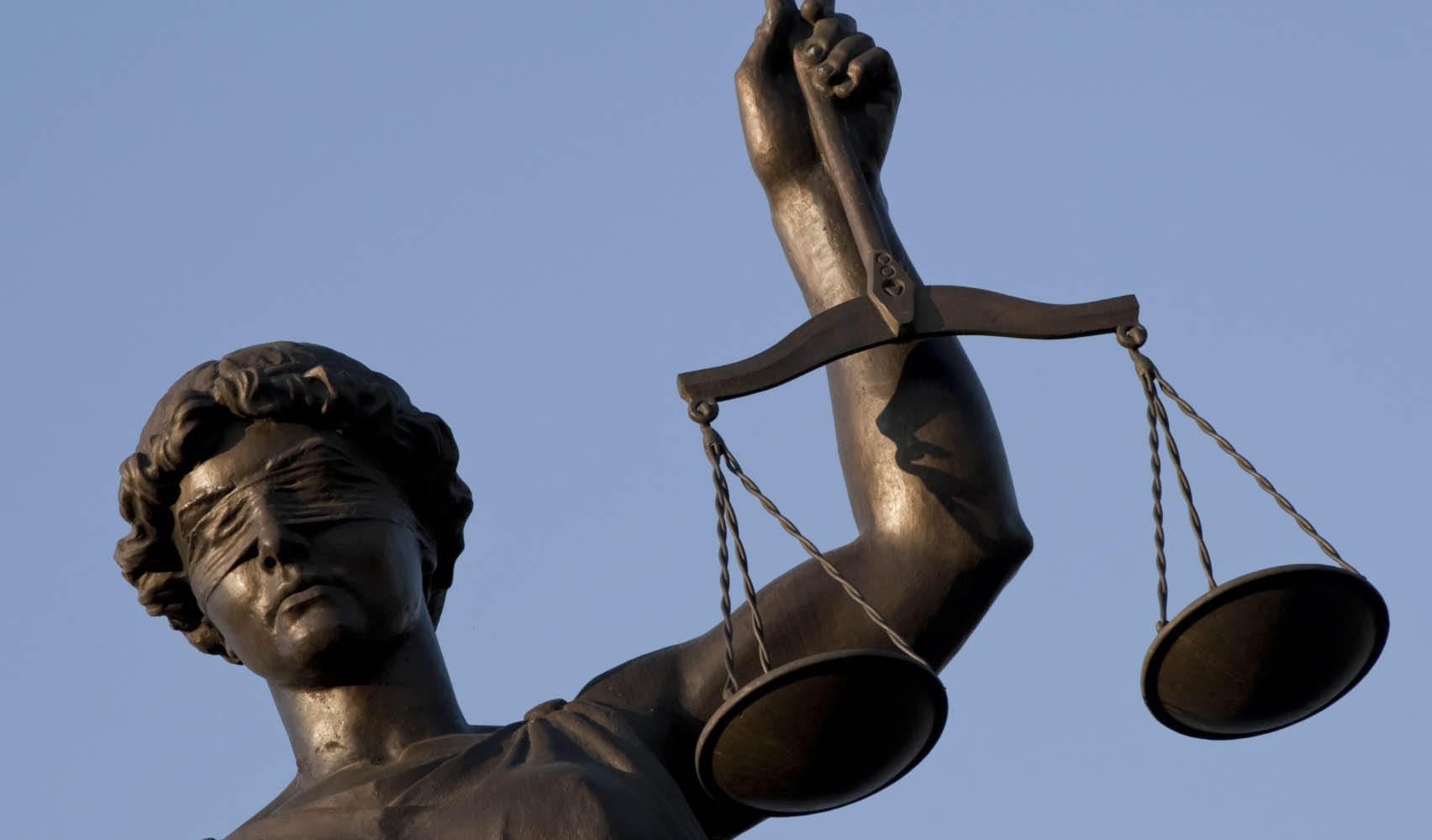 Against blue sky a Justice statue; Shutterstock ID 33202687; PO: aol; Job: production; Client: drone